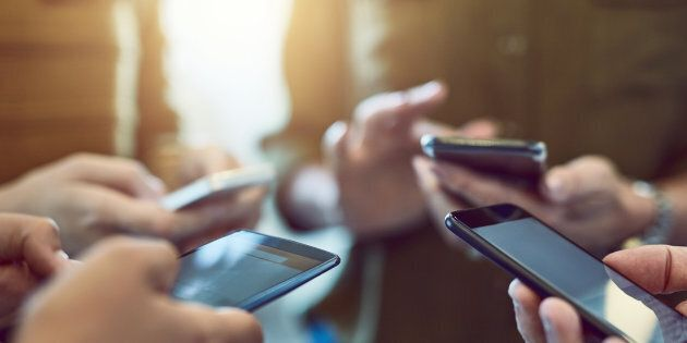 A group of people are seen using smartphones. A non-profit advocacy group is urging the CRTC to launch...