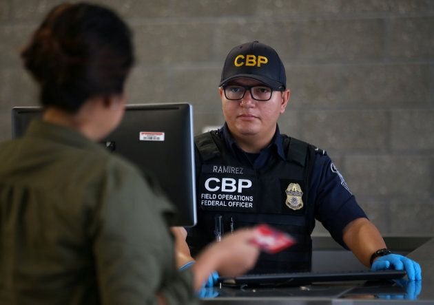 A U.S. Customs and Border Patrol officer interviews people entering the United States from Mexico at...