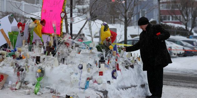 A man puts a candle at the memorial near the site of a fatal shooting at the Quebec Islamic Cultural...