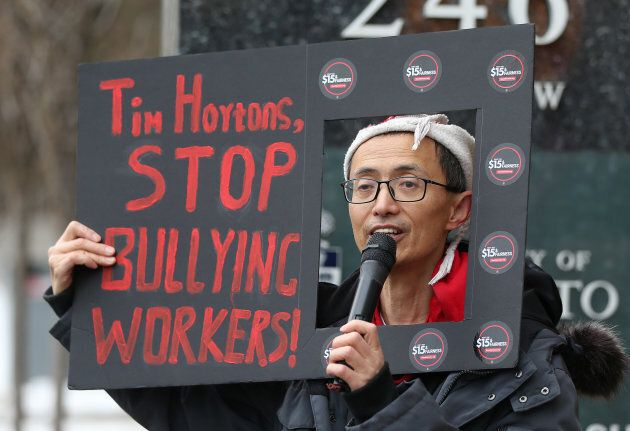 Protesters hold signs outside a Tim Horton's location in Toronto.