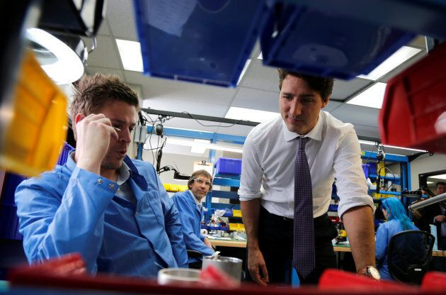 Prime Minister Justin Trudeau (R) talks to employees as he tours Kinova Robotics, a company that designs...