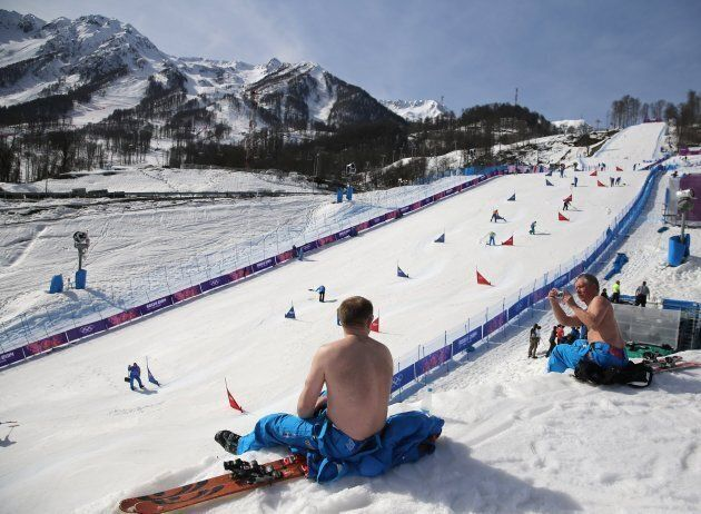 Course workers take their shirts off to enjoy warm weather during the snowboard parallel slalom competition...