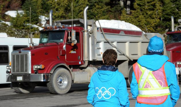 Volunteers look on as a truck loaded with snow arrives at Cypress Mountain ahead of the 2010 Vancouver...
