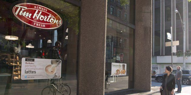 A woman walks pass a Tim Hortons in Toronto on Wednesday Aug. 2, 2017. The parent company of Tim Hortons...
