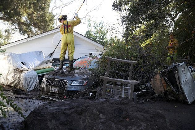 A Cal Fire firefighter looks through a car next to a home that was destroyed by a mudslide on Jan. 12,...