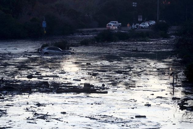 A car is submerged in muddy water in a flooded section of Highway 101 car on Jan. 11, 2018 in Montecito,