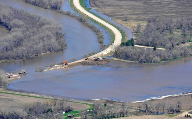 Water flows out of Assiniboine River after workers cut an intentional release through a dike at the Hoop...