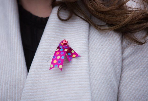 Trisha Lees, a friend of the family, wears a ribbon in memory of Chloe and Aubrey Berry while attending...