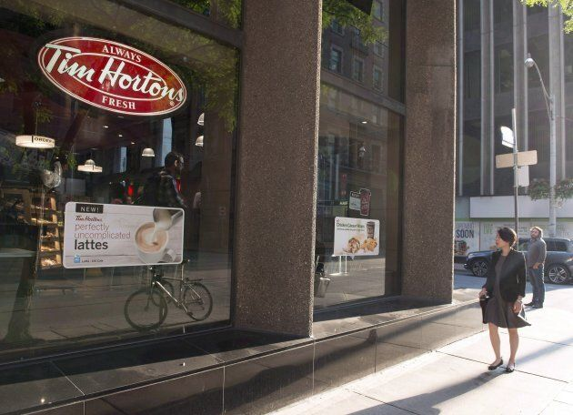 A woman walks pass a Tim Hortons in Toronto on Aug. 2,