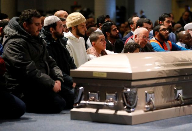 Mourners listen during funeral services for three of the victims of the deadly shooting at the Quebec...