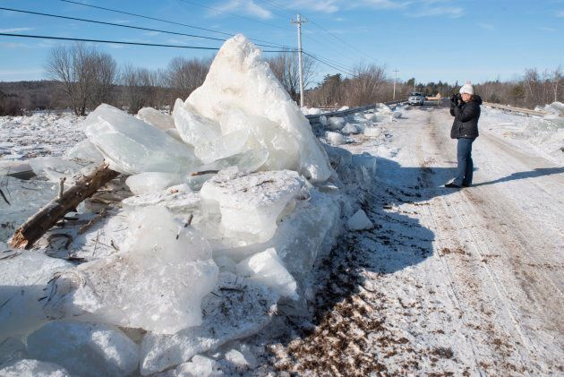 Karen Yorke-Doucette takes a photo of the ice piled up along side of Route 101 in Hoyt, N.B., on Jan....