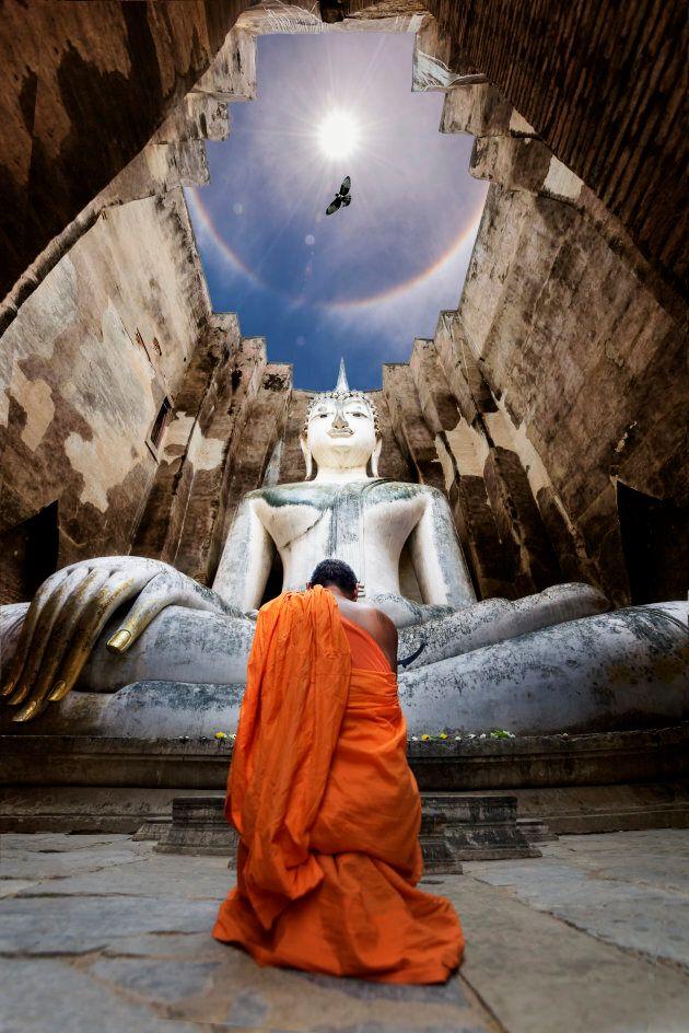 Monks worship Buddha statue Wat Si Chum in Sukhothai historical park, Thailand.