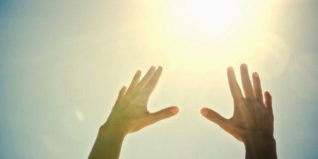Mixed race woman's hands reaching toward sun