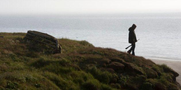 WAINWRIGHT, AK - JULY 18: A teenager explores the shoreline near the Chukchi Sea in Wainwright, Alaska...