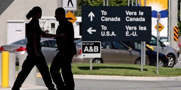 Canadian border guards are silhouetted as they replace each other at an inspection booth at the Douglas...