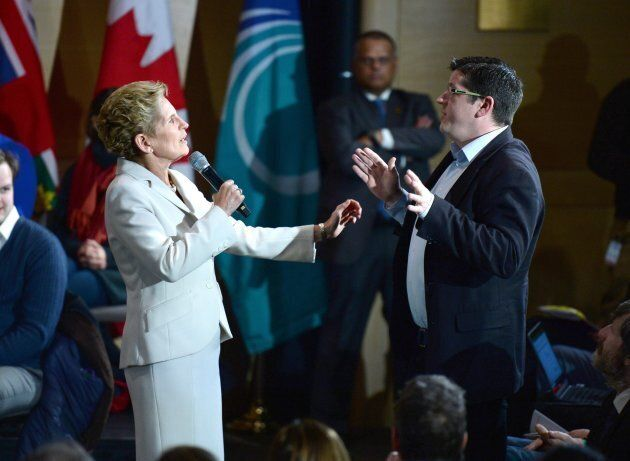 Will Hickie, a member of the public in attendance, asks a question as he interrupts Ontario Premier Kathleen...