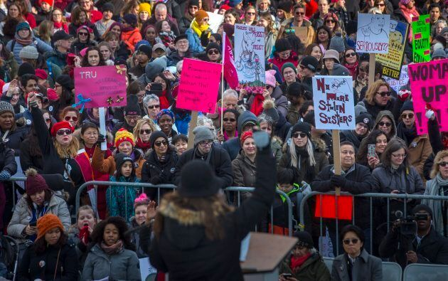 People listen to a speaker as they gather in Nathan Phillips Square, before embarking on a Women's March...