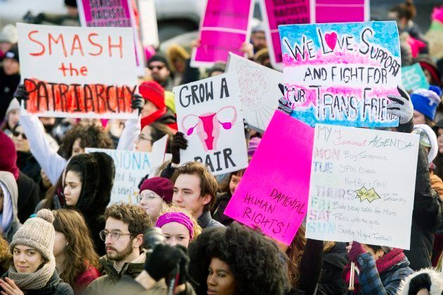 People hold up signs during a women's march in Montreal on