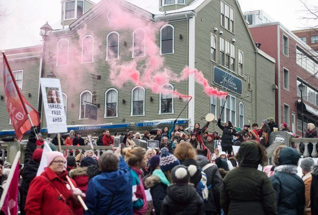 Pink flares are lit during a Women's March in solidarity with women and human rights groups across the...