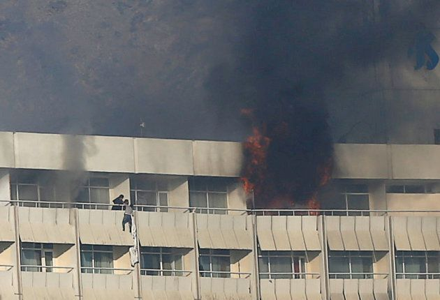 A man tries to escape from a balcony at Kabul's Intercontinental Hotel during an attack by gunmen in...