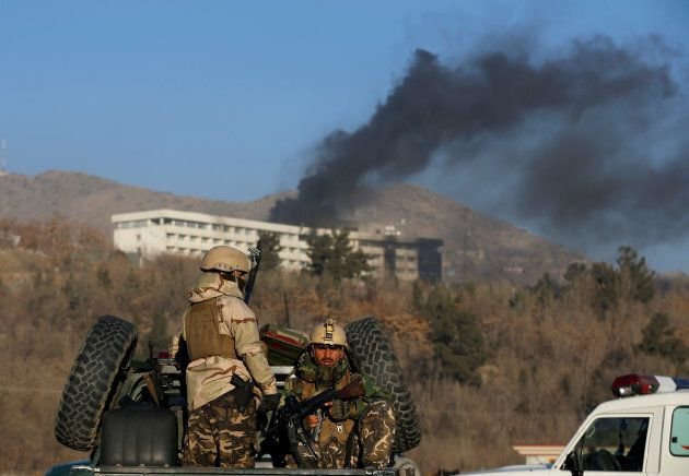 Afghan security forces keep watch as smoke rises from the Intercontinental Hotel in Kabul, Afghanistan...