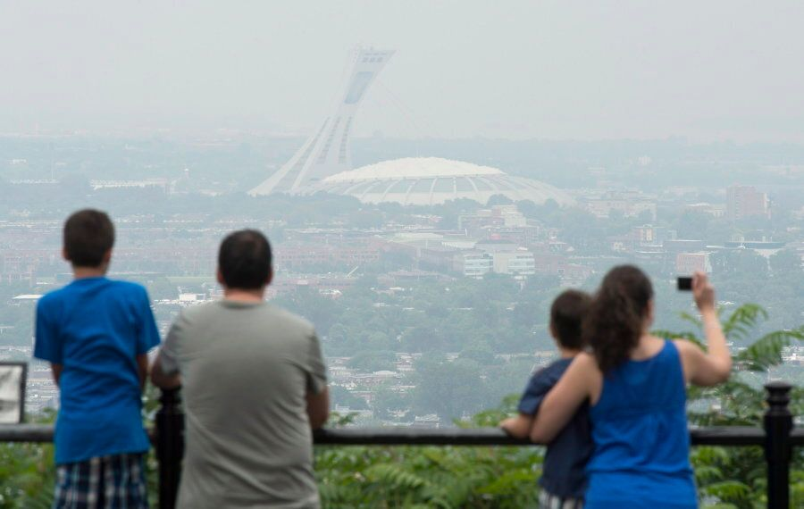Tourists look over at the Olympic Stadium in the smog-covered city of Montreal on July 3,