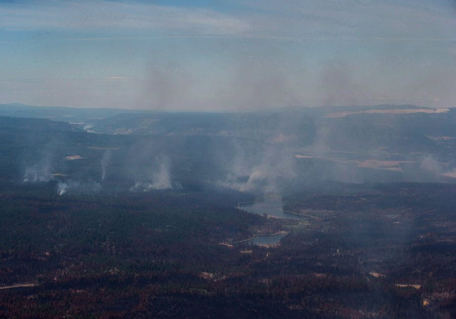 Smoke from wildfires fills the air and burned trees are seen in this aerial view from a Canadian Forces...