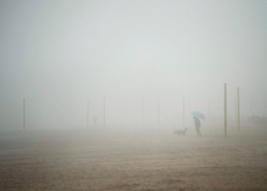 A man walks his dog on the beach during a foggy rainy day in Toronto on March 10,