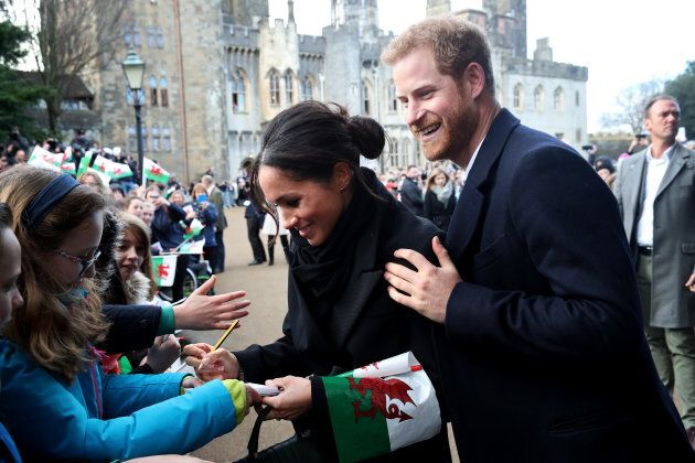 Prince Harry and Meghan Markle sign autographs and shake hands with children at Cardiff Castle on Jan. 18.
