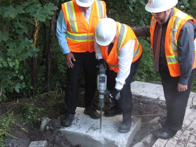 Former Montreal Mayor Denis Coderre uses a jackhammer to destroy a concrete foundation laid for an unauthorized...
