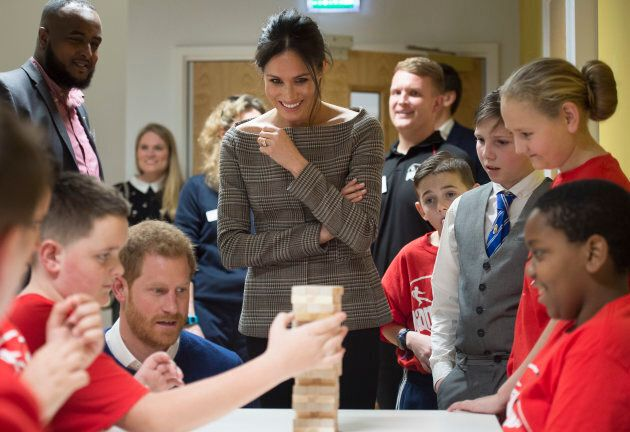 Prince Harry and Meghan Markle watch a game of Jenga during their visit to Star Hub on Jan. 18,