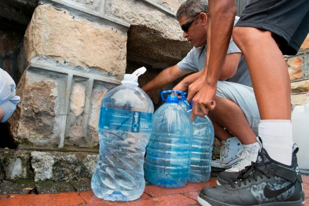 People collect drinking water from pipes fed by an underground spring, in St. James, about 25 kilometres from Cape Town's city centre, on Jan. 19, 2018.