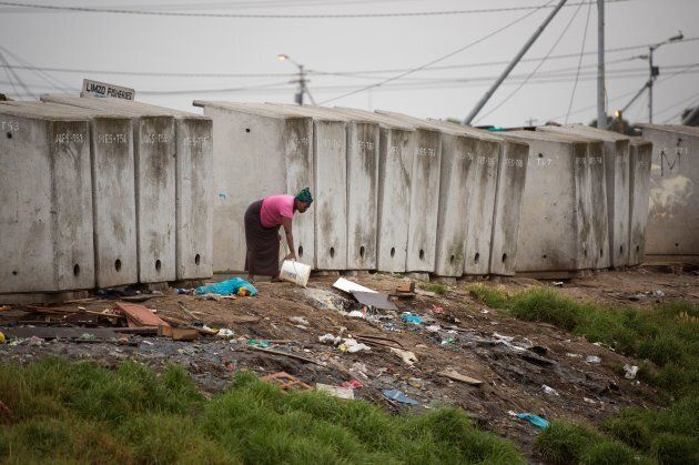 A woman throws out waste water next to a line of toilets in an informal settlement in Langa, a mostly impoverished township, about 10 kilometres from the centre of Cape Town, on Nov. 12, 2017.