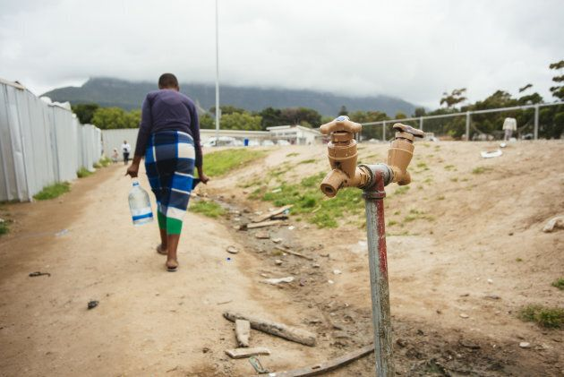 A resident carries a plastic container of water after filling from the communal tap in the Imizamo Yethu township outside Cape Town, South Africa on Nov. 13, 2017.