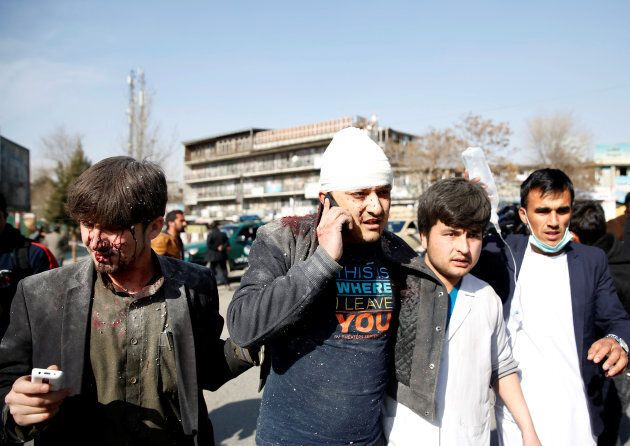 People assist an injured man after a blast in Kabul, Afghanistan on Jan. 27,