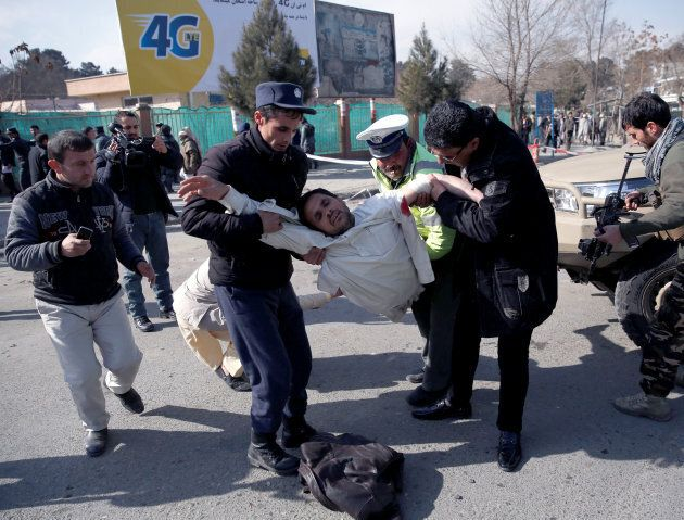 People carry an injured man after a blast in Kabul, Afghanistan on Jan. 27,