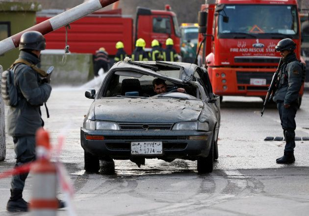 Afghan police officers keep watch while a man drives his damaged car at the site of a car bomb attack...