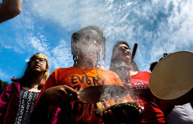 A protester participates in a smudge in front of the covered statue of Halifax founder Edward Cornwallis,...