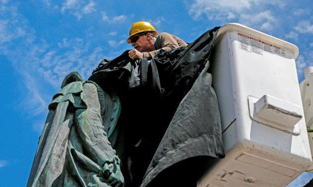 A municipal employee covers the statue of Halifax founder Edward Cornwallis, who issued a bounty on the...
