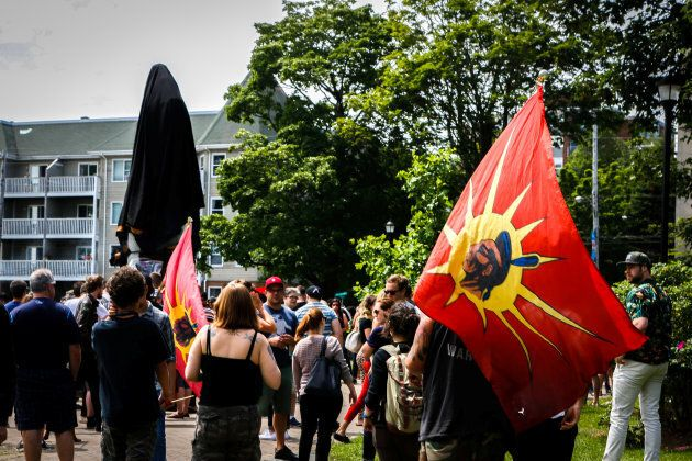 Protesters gather around a covered statue of Halifax founder Edward Cornwallis, who had issued a bounty on the heads of Indigenous people, during a protest in Halifax on July 15, 2017.