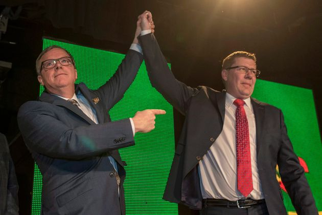 Outgoing Saskatchewan Premier Brad Wall takes a victory stance with Premier-Designate Scott Moe at the...