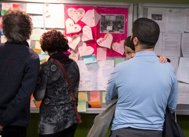 People look at messages of sympathy during a gathering at the Centre Islamique de Quebec, marking the...