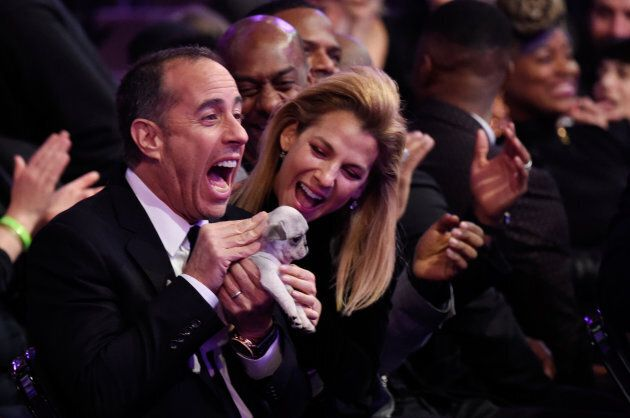Comedian Jerry Seinfeld receives a consolation puppy during the 60th Annual Grammy
