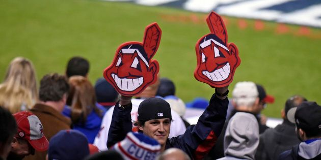 A fan holds up two Chief Wahoo heads during Game 1 of the 2016 World Series between Chicago and Cleveland...