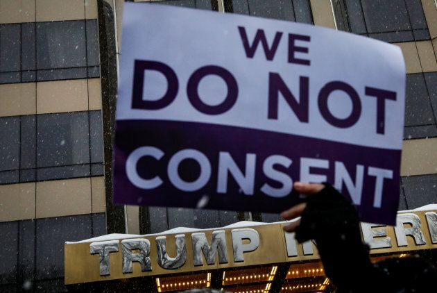 A protester holds a sign up during a #MeToo demonstration outside Trump International hotel in New York...
