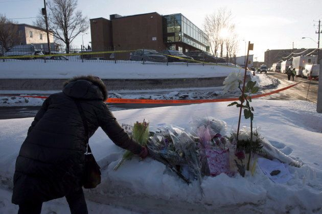 A woman places flowers near a mosque where a shooting the previous night left six people dead in Quebec