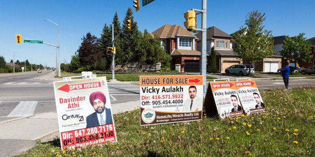 Open house signs are displayed on the side of a road in the Toronto suburb of Brampton, Sat. May 20,...