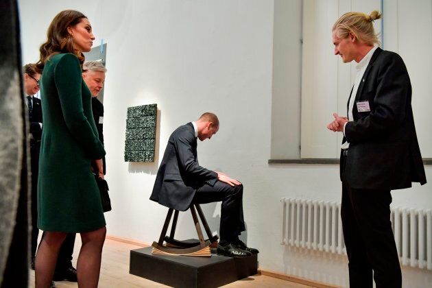 The Duke of Cambridge tries out a chair as Catherine and others look on.