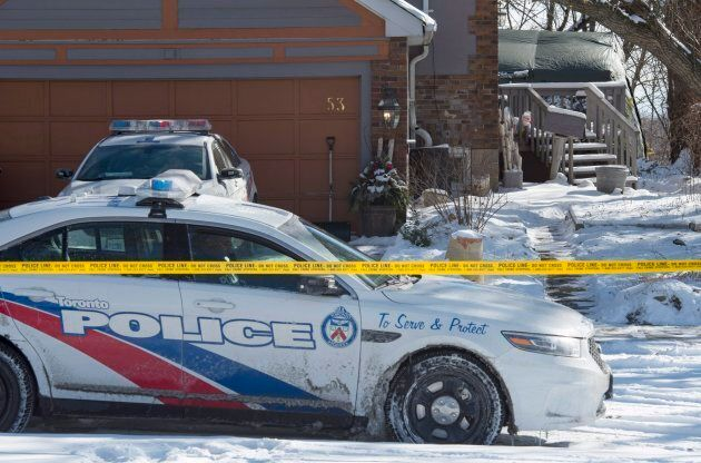 Police stand guard at a house on Mallory Crescent in Toronto on Tuesday. Police are investigating the...