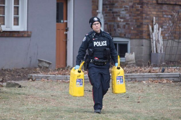 A police officer carries containers outside a house on Mallory Crescent in Toronto, where Bruce McArthur...